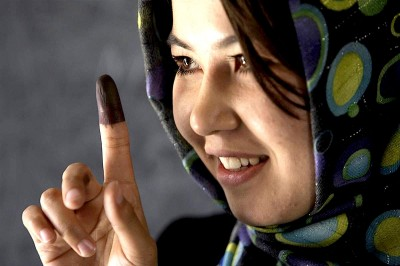 An Afghan woman reveals the ink on her finger – indicating that she cast her vote.